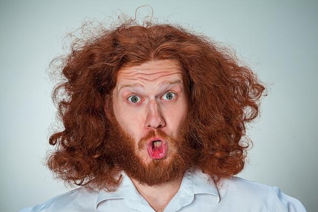 Portret van een jonge man met lang rood haar en met een geschokte gelaatsuitdrukking op een grijze achtergrond