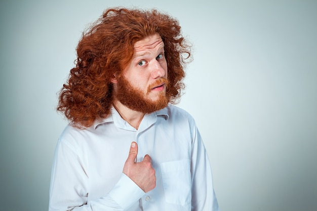 Portret van een jonge man met lang rood haar en met een geschokte gezichtsuitdrukking op grijs wijzend naar zichzelf