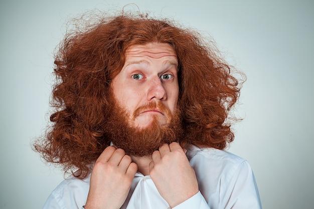 Portret van een jonge man met lang rood haar en met een geschokte gezichtsuitdrukking op grijs
