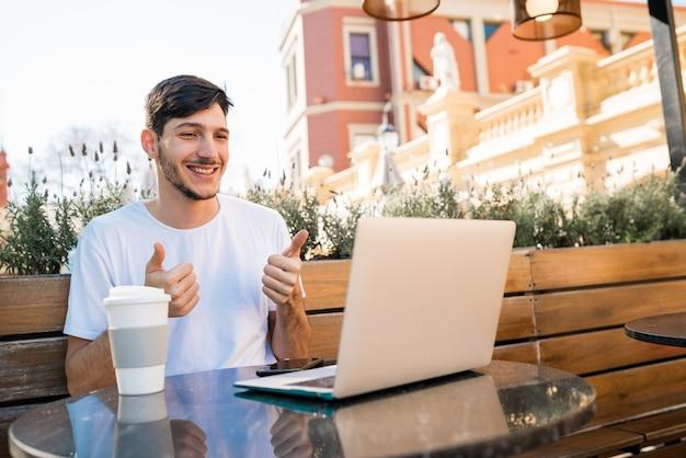 Portret van een jonge man met laptop skype videochat bij coffeeshop. skype en technologie concept.