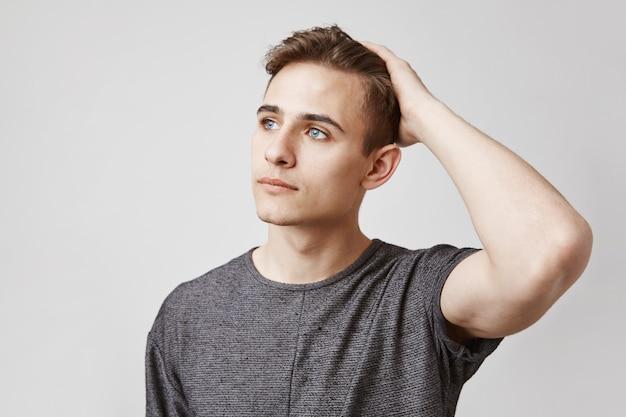 Portret van een jonge man met mooie blauwe ogen aan te raken zijn hoofd.