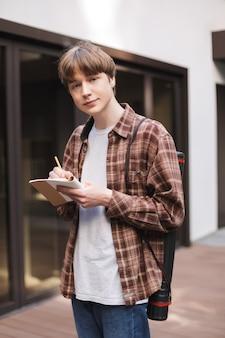 Portret van een jonge man met notitieboekje en potlood in handen en dromerig