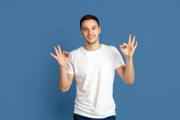 Portret van een jonge man met ok teken geïsoleerd op blauwe studio wall
