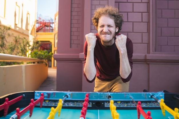 Portret van een jonge man met plezier en tafelvoetbal spelen