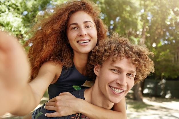 Portret van een jonge man met roodharige vrouw op zijn rug