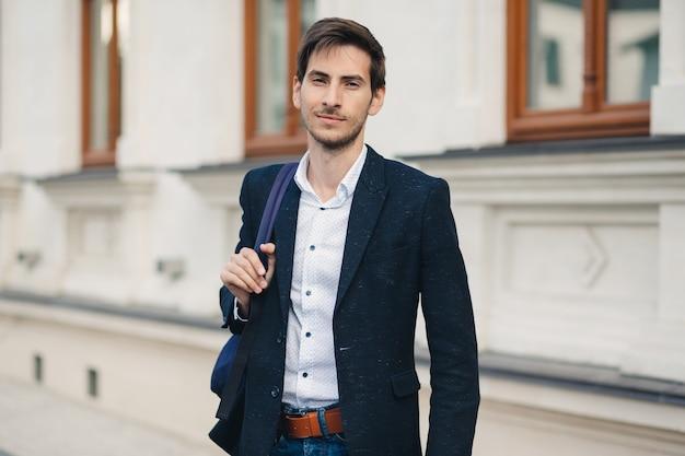 Portret van een jonge man met rugzak in de stad