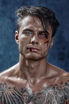 Portret van een jonge man met slagen, wonden, schaafwonden en bloed op zijn gezicht