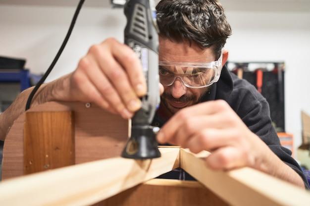 Portret van een jonge man met veiligheidsbril die met een dremel-hulpmiddel werkt