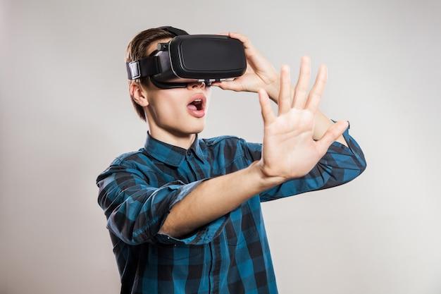 Portret van een jonge man met virtual reality-headset. binnen, geïsoleerd op een grijze achtergrond.