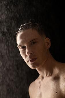 Portret van een jonge man met waterdruppels op zwarte muur