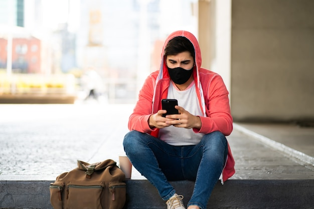 Portret van een jonge man met zijn mobiele telefoon terwijl hij buiten op straat zit. man met gezichtsmasker. stedelijk concept. Premium Foto
