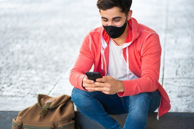 Portret van een jonge man met zijn mobiele telefoon terwijl hij buiten op straat zit. man met gezichtsmasker. stedelijk concept.