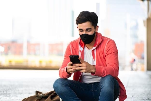 Portret van een jonge man met zijn mobiele telefoon terwijl hij buiten op straat zit