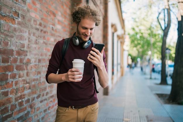 Portret van een jonge man met zijn mobiele telefoon tijdens het wandelen buiten in de straat. communicatie en stedelijk concept.