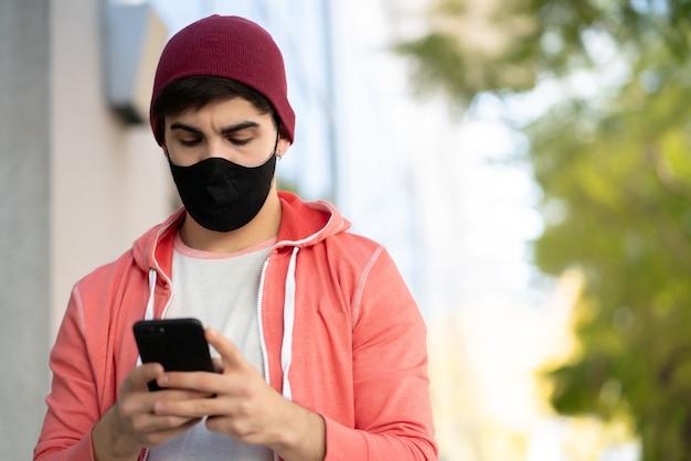 Portret van een jonge man met zijn mobiele telefoon tijdens het wandelen buiten op straat. man met gezichtsmasker. stedelijk concept. Premium Foto