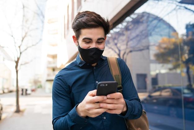 Portret van een jonge man met zijn mobiele telefoon tijdens het wandelen buiten op straat. nieuw normaal levensstijlconcept. stedelijk concept.