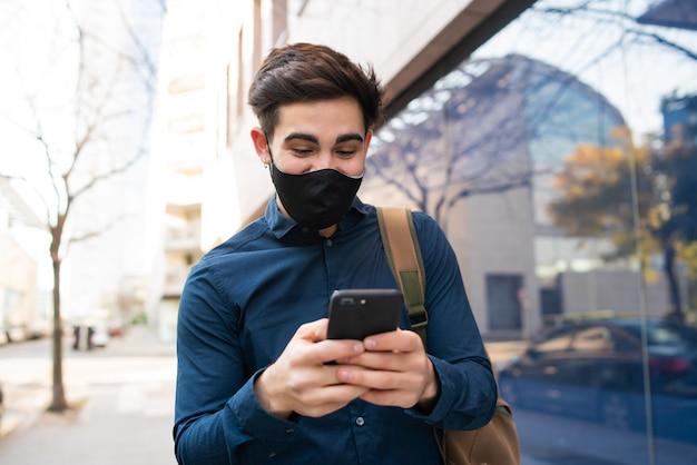 Portret van een jonge man met zijn mobiele telefoon tijdens het wandelen buiten op straat