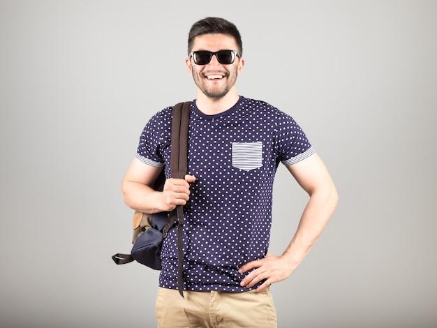 Portret van een jonge man met zonnebril en rugzak