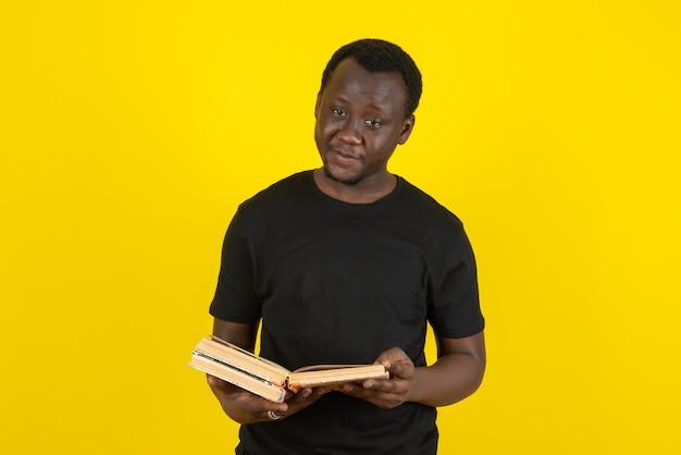 Portret van een jonge man model met boeken tegen gele muur