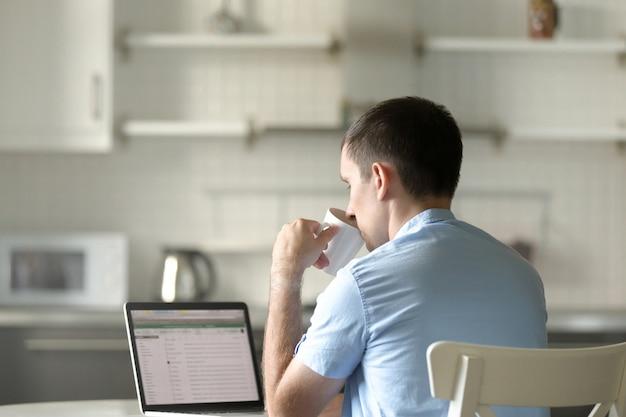 Portret van een jonge man op bureau met een laptop, drinken