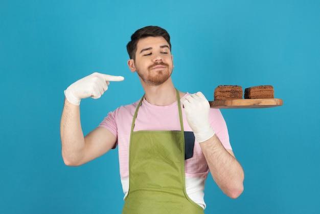 Portret van een jonge man op een blauwe die cakeplakken vasthoudt en er met de vinger naar wijst.