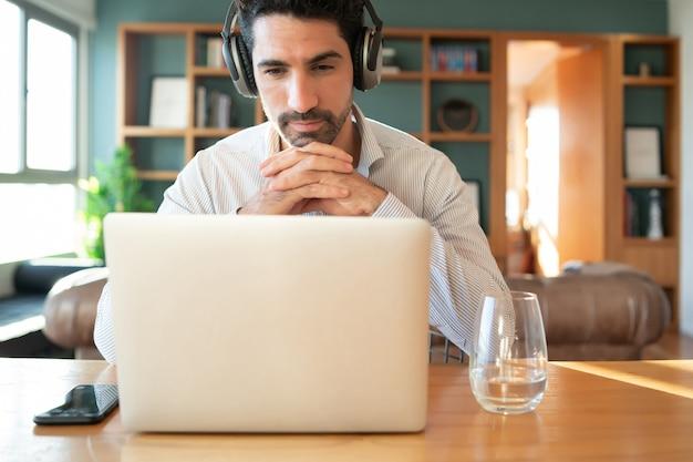 Portret van een jonge man op een werk video-oproep met laptop vanuit huis. thuiskantoor concept. nieuwe normale levensstijl.