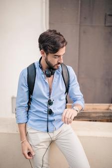 Portret van een jonge man op tijd kijken op wacht