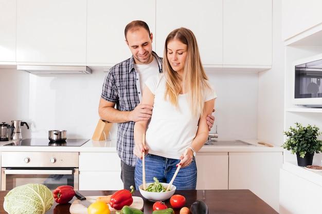Portret van een jonge man op zoek naar haar vrouw de voorbereiding van de salade