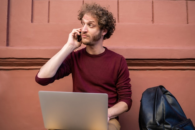 Portret van een jonge man praten aan de telefoon en zijn laptop gebruikt terwijl hij buiten zit. technologie en levensstijlconcept.
