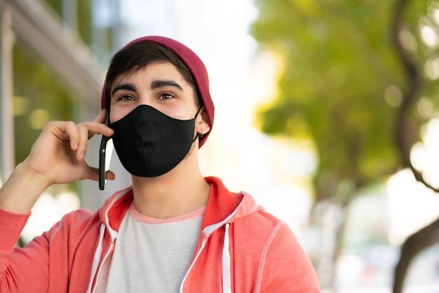 Portret van een jonge man praten aan de telefoon tijdens het wandelen buiten op straat. man met gezichtsmasker. stedelijk concept.