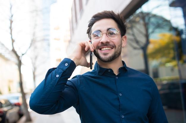 Portret van een jonge man praten aan de telefoon tijdens het wandelen buiten op straat. stedelijk concept.