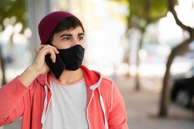 Portret van een jonge man praten aan de telefoon tijdens het wandelen buiten op straat.