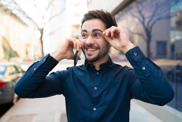 Portret van een jonge man praten aan de telefoon tijdens het wandelen buiten op straat