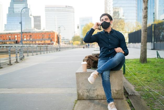 Portret van een jonge man praten aan de telefoon zittend op een bankje buiten. nieuw normaal levensstijlconcept.
