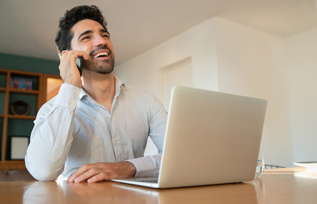 Portret van een jonge man praten op zijn mobiele telefoon en werken vanuit huis met laptop. thuiskantoor concept