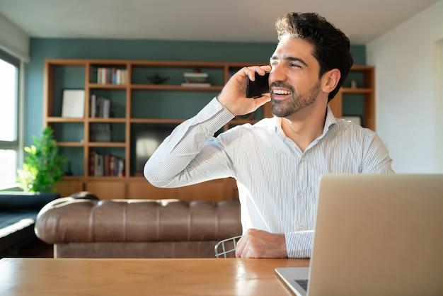 Portret van een jonge man praten op zijn mobiele telefoon en werken vanuit huis met laptop.