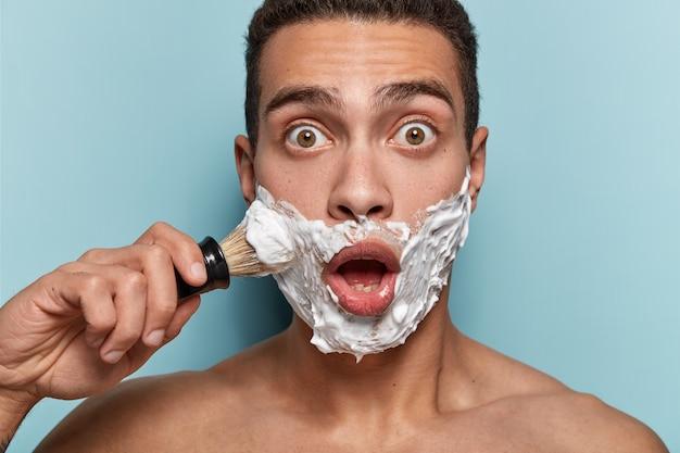 Portret van een jonge man scheerschuim toe te passen
