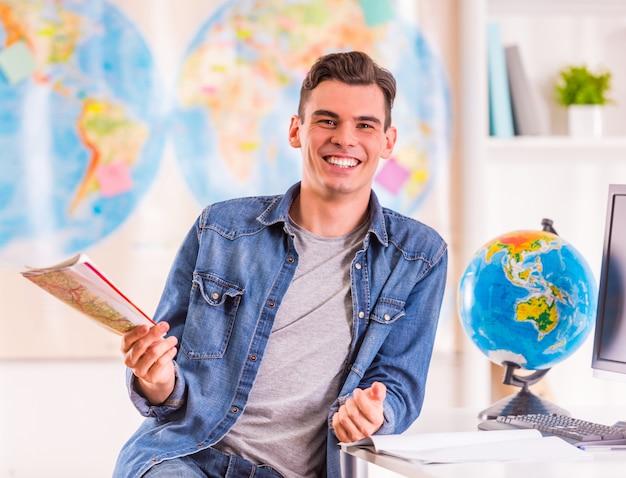 Portret van een jonge man selecteert voor de reis met behulp van een kaart.