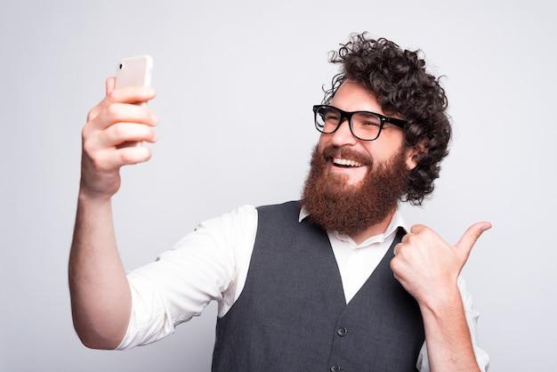 Portret van een jonge man selfie te nemen en duim opdagen