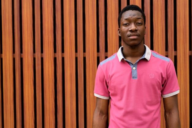 Portret van een jonge man tegen houten poort buitenshuis