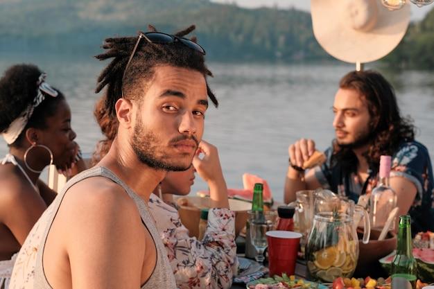 Portret van een jonge man tijdens het diner aan tafel samen met zijn vrienden buitenshuis