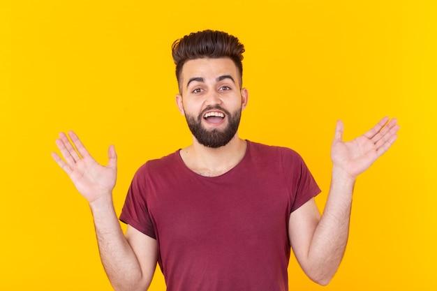 Portret van een jonge man verrast met dauw in een overhemd dat tegen een gele muur doseert. concept van nieuws en promo. copyspace