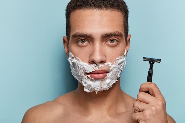 Portret van een jonge man zijn baard scheren