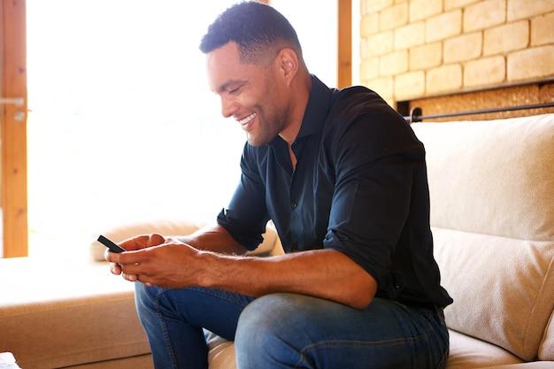 Portret van een jonge man zittend op een bank en het gebruik van mobiele telefoon thuis