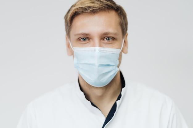 Portret van een jonge mannelijke arts die een steriel masker draagt dat op een witte muur wordt geïsoleerd