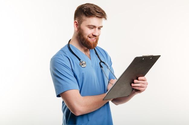 Portret van een jonge mannelijke arts die op klembord schrijft