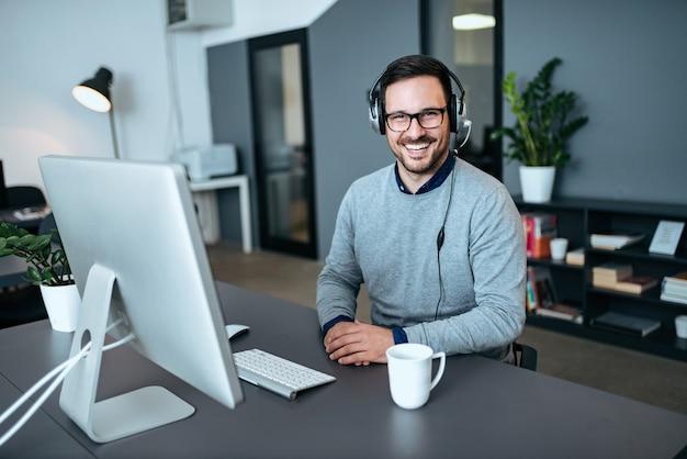 Portret van een jonge mannelijke call centrewerknemer in zijn bureau.
