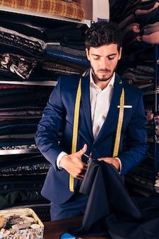 Portret van een jonge mannelijke kleermaker die in zijn workshop werkt