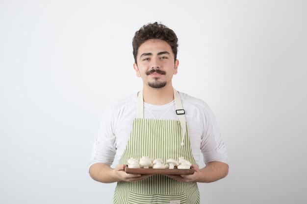 Portret van een jonge mannelijke kok die rauwe champignons op wit houdt