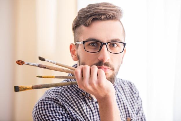 Portret van een jonge mannelijke kunstenaar met borstels voor het schilderen.